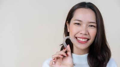 woman smiling holding invisalign clear plastic tray l invisalign mesquite tx